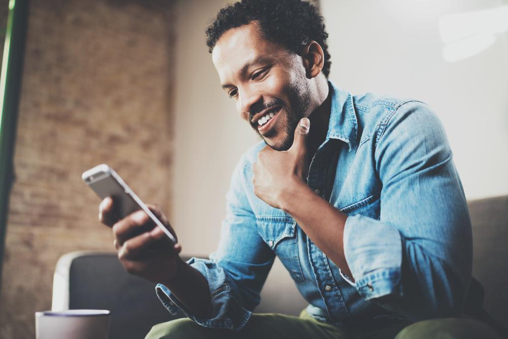 Man smiling while looking at phone