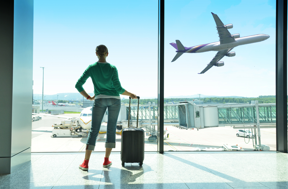 Woman standing in airport looking at airplane